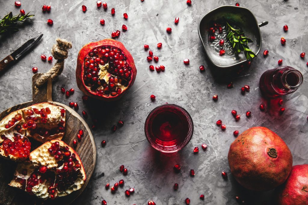 Red pomegranate juice in a glass, ripe and cut pomegranate and a sprig of mint on a gray background